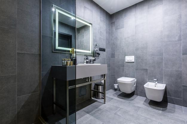 Wnętrze łazienki z pięknymi płytkami ceramicznymi i prysznicem w kolorze szarym ciemnym