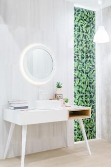Wnętrze łazienki z umywalką i białym ręcznikiem.