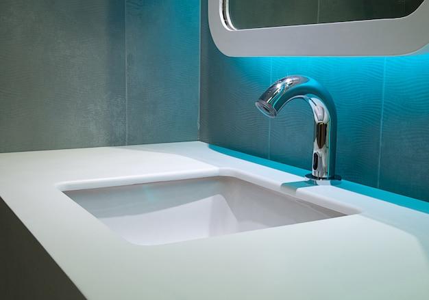Wnętrze łazienki z umywalką i kranem oraz lustrem nowoczesny design łazienki,