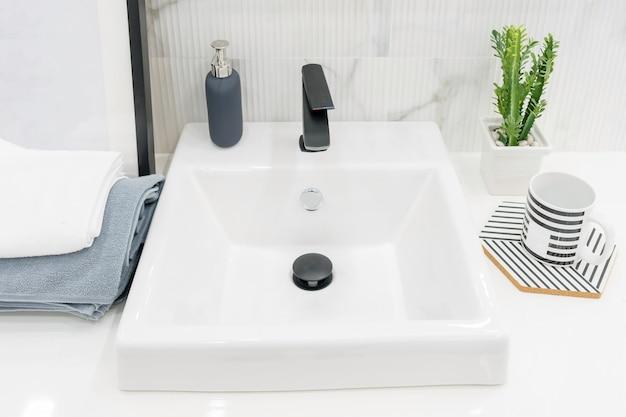 Wnętrze łazienki z umywalką i kranem.