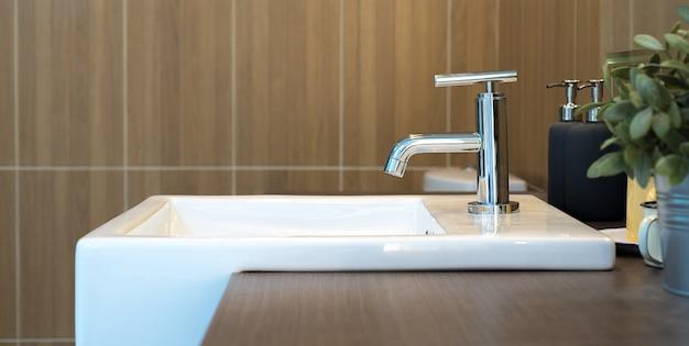 Wnętrze łazienki z umywalką i kranem