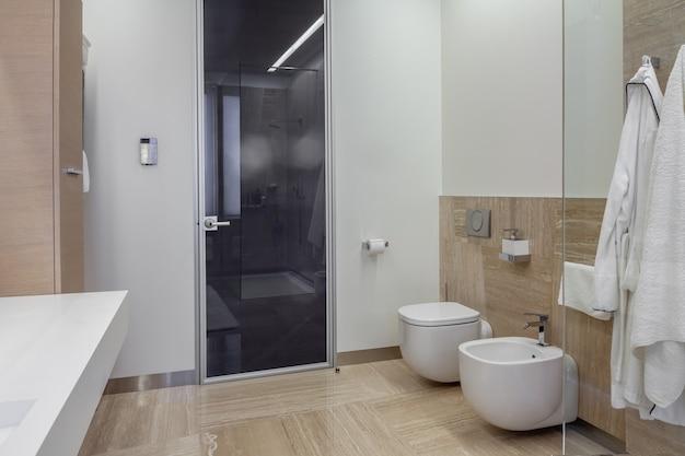 Wnętrze łazienki z wiszącą toaletą i bidetem oraz kabiną prysznicową