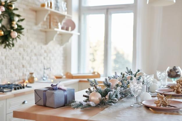 Wnętrze lekka kuchnia z bożonarodzeniowym wystrojem i drzewem. biała kuchnia w klasycznym stylu. boże narodzenie w kuchni. jasna kuchnia w białych odcieniach z bożym narodzeniem. świąteczne nakrycie stołu.