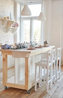 Wnętrze lekka kuchnia z bożonarodzeniowym wystrojem i drzewem. biała kuchnia w klasycznym stylu. boże narodzenie w kuchni. jasna kuchnia w białych odcieniach z bożym narodzeniem.