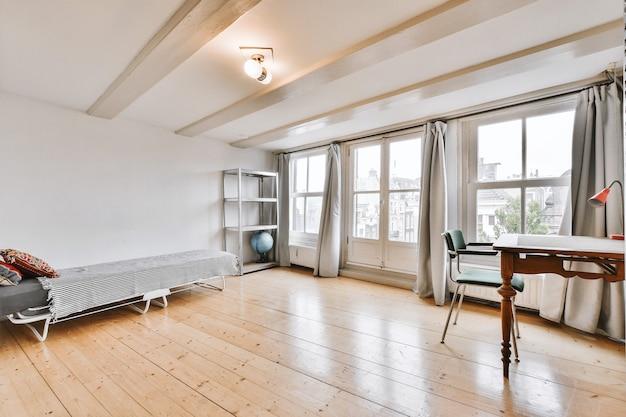 Wnętrze lekkiego biura w domu z drewnianym biurkiem i półką w pobliżu okna z zasłonami