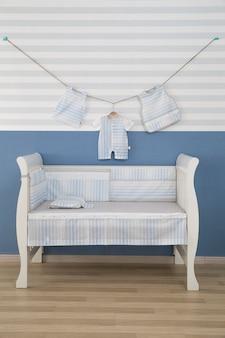 Wnętrze lekkiego przytulnego pokoju dziecięcego z łóżeczkiem i pościelą