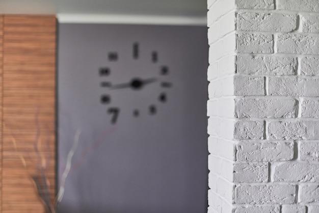Wnętrze mieszkania na poddaszu, miejsce na kopię. biały mur z cegły i zegar ścienny w salonie. przetworzone kondominium na poddaszu na poddaszu w budynku przemysłowym