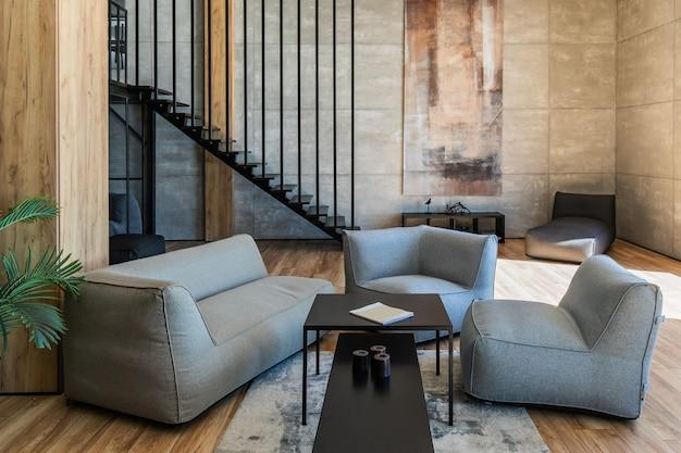 Wnętrze młodego kawalera w stylu loftu z miękkimi meblami na pierwszym planie, metalowymi schodami i szafą w tle