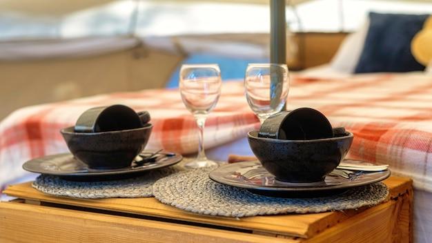 Wnętrze namiotu z łóżkiem i naczyniami ustawione na glamping, z bliska