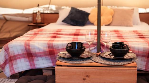 Wnętrze namiotu z łóżkiem i naczyniami w glampingu