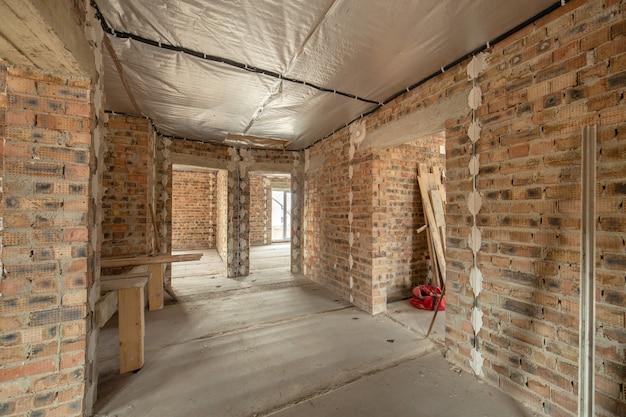 Wnętrze niedokończonego domu z cegły z betonową podłogą i gołymi ścianami gotowymi do tynkowania w budowie. rozwój nieruchomości