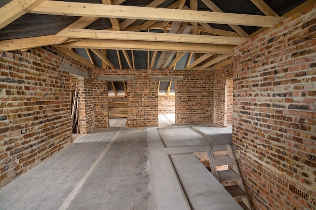 Wnętrze nieukończonego domu murowanego z posadzką betonową, ścianami gołymi gotowymi do tynkowania oraz poddaszem z drewnianą ramą dachową w budowie.