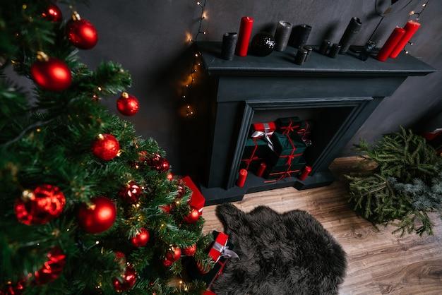 Wnętrze nowego roku 2021 ze świecami, żarówkami i bokeh. pokój urządzony na boże narodzenie. choinka z prezentami