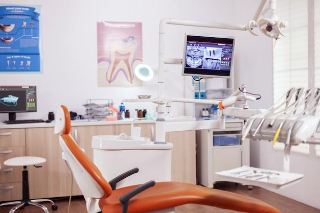 Wnętrze nowoczesnego gabinetu dentystycznego i fotela lekarskiego. gabinet stomatologiczny, w którym nikogo nie ma i pomarańczowy sprzęt do leczenia jamy ustnej.