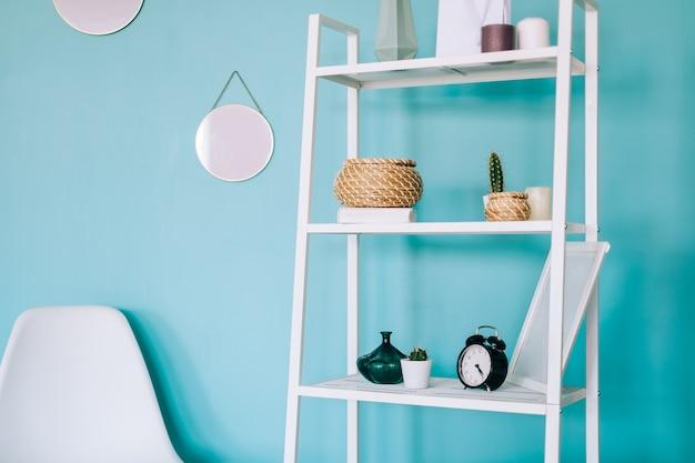 Wnętrze nowoczesnego pokoju w kolorze białym z regałami i niebieskimi ścianami.