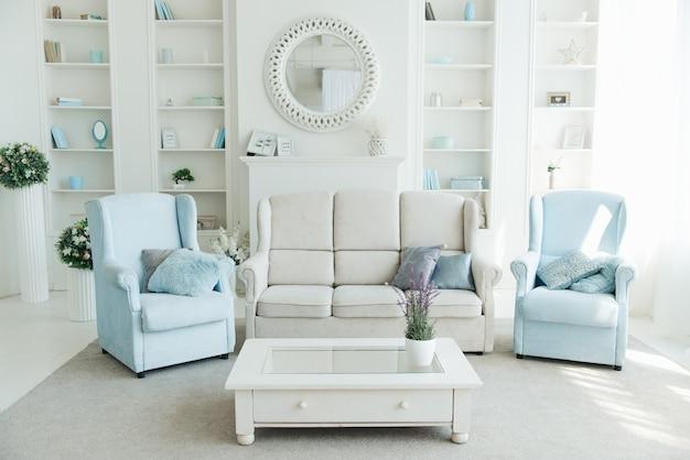 Wnętrze nowoczesnego salonu z białą sofą, niebieskimi fotelami i półką na książki