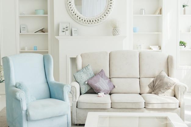 Wnętrze nowoczesnego salonu z białą sofą, niebieskimi fotelami i regałem z tyłu