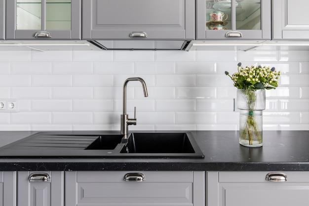 Wnętrze nowoczesnej kuchni. ciemny blat i zlew, szare fronty szafek. wazon z kwiatami ozdabia stół