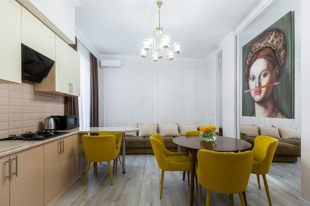 Wnętrze nowoczesnej kuchni, duży pokój o pięknym wystroju w pastelowych kolorach, szarości i żółci