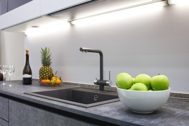 Wnętrze nowoczesnej kuchni rozjaśnia blat z szarego kamienia z luksusową umywalką i baterią, owocowy ananas