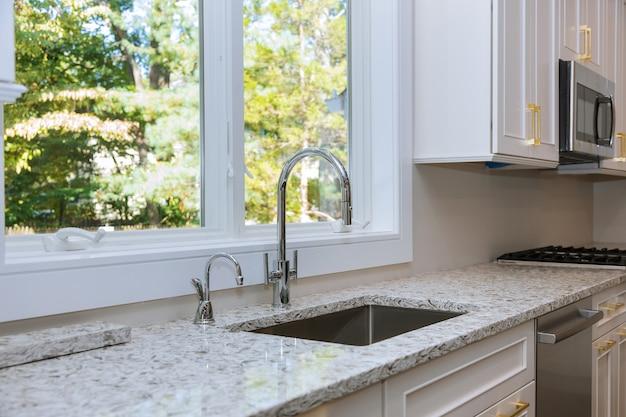 Wnętrze nowoczesnej kuchni z urządzeniami na blacie kuchennym, marmurowy blat z białymi szafkami kuchennymi