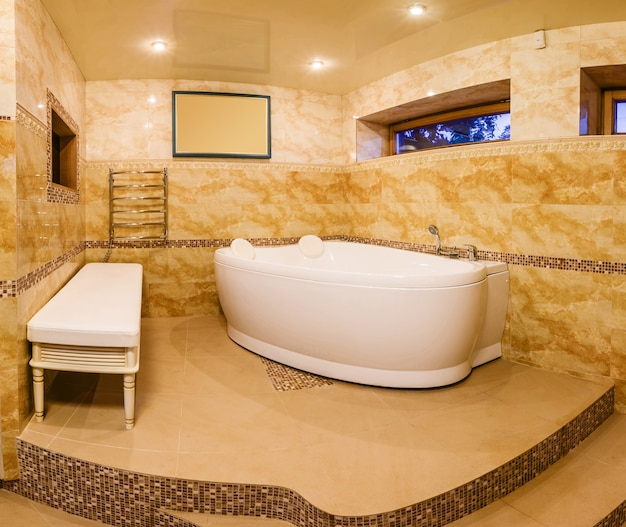 Wnętrze nowoczesnej łazienki domu z marmurowymi płytkami i jacuzzi