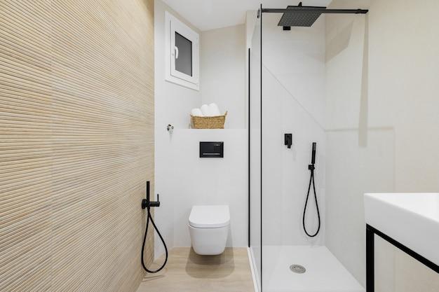 Wnętrze nowoczesnej łazienki w biało-beżowej kolorystyce w odnowionym mieszkaniu strefa prysznicowa i toaleta z czarnymi kranami, ręczniki oraz wyłożona kafelkami podłoga i ściany