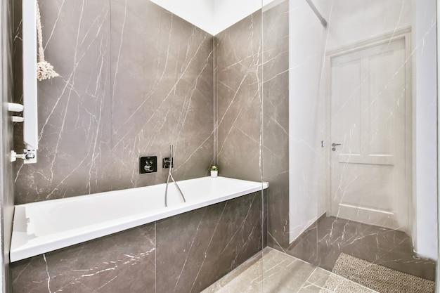 Wnętrze nowoczesnej łazienki z wanną i marmurowymi ścianami
