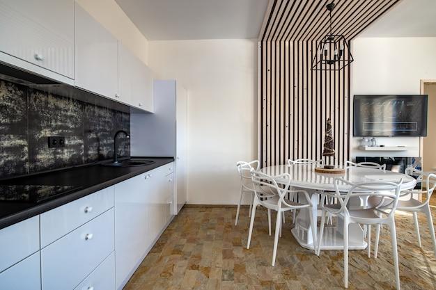 Wnętrze nowoczesnej przestronnej kuchni z białymi ścianami, dekoracyjnymi drewnianymi elementami, współczesnymi meblami i dużą miękką kanapą.
