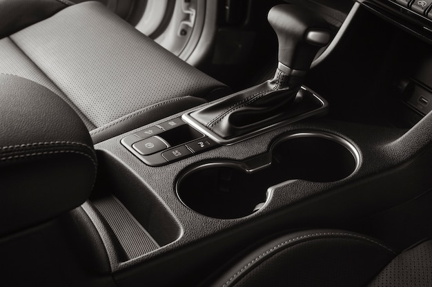 Wnętrze pojazdu z czarnymi skórzanymi siedzeniami i automatyczną dźwignią zmiany biegów