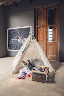 Wnętrze pokoju dziecięcego z namiotem zabaw i zabawkami