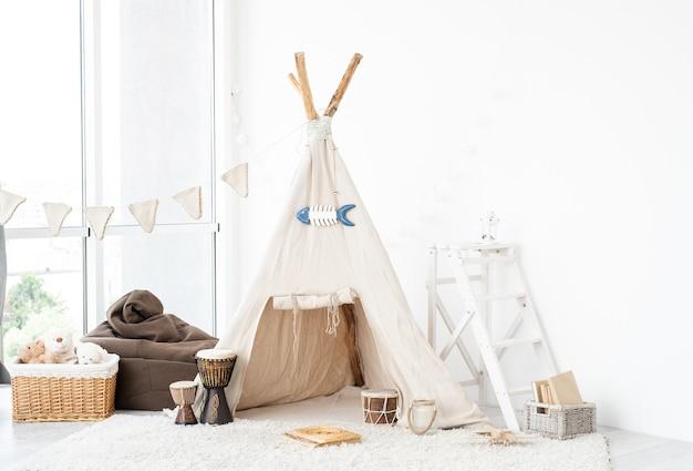 Wnętrze pokoju dziecięcego z zabawkami do wigwamu i bębnami djembe