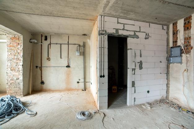 Wnętrze pokoju mieszkalnego z gołymi ścianami i sufitem w budowie.