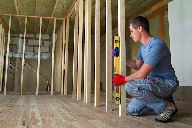 Wnętrze pokoju na poddaszu z izolowanym sufitem i dębową podłogą w trakcie przebudowy. młody profesjonalny pracownik używa poziomu instalując drewnianą ramę do przyszłych ścian. koncepcja remontu i poprawy.