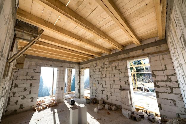 Wnętrze pokoju w budowie i renowacji. energooszczędne ściany z pustych pustaków izolacyjnych z pianki, drewniane belki stropowe i rama dachowa.