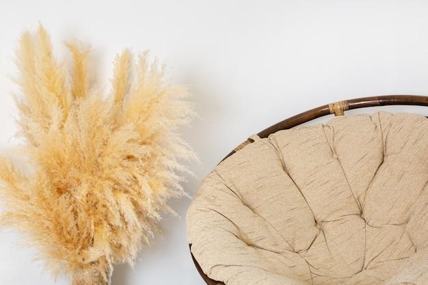 Wnętrze pokoju, wiklinowe krzesło, trzciny suchej trawy pampasowej w szklanym wazonie i krzesło na drewnianej podłodze