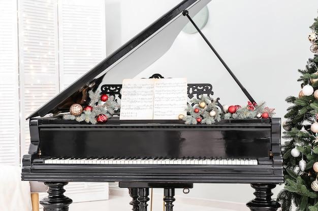 Wnętrze pokoju z fortepianem udekorowane na boże narodzenie