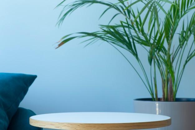 Wnętrze pokoju z pustą ścianą ze stolikiem kawowym i zieloną rośliną tropikalną