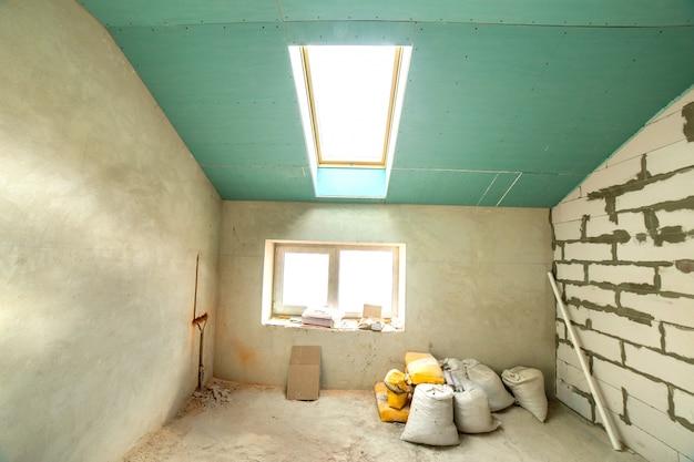 Wnętrze pokoju z pustymi ścianami i sufitem w budowie.