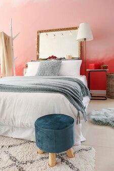 Wnętrze pokoju z wygodnym łóżkiem przy różowej ścianie