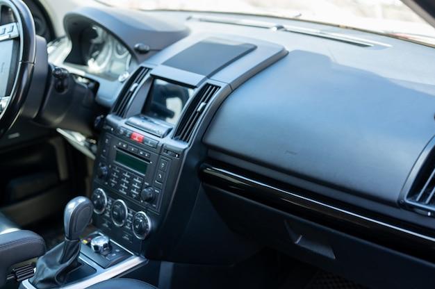 Wnętrze przedniego fotela samochodowego. wnętrze prestiżowego nowoczesnego samochodu. wygodne skórzane fotele. kokpit z czarnej perforowanej skóry. wyświetlacz multimedialny, kierownica, dźwignia zmiany biegów i deska rozdzielcza.