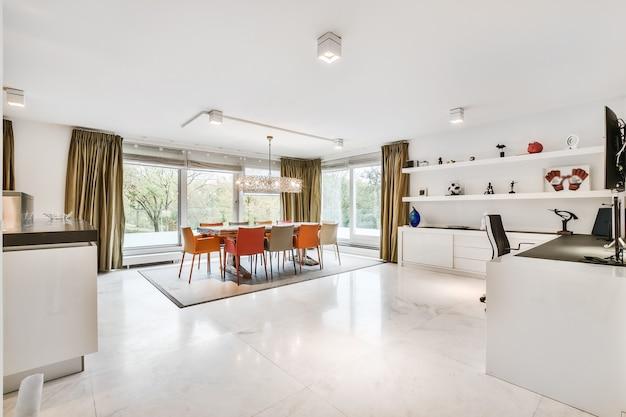 Wnętrze przestronnego jasnego pokoju z jadalnią i miejscem do pracy w nowoczesnym mieszkaniu