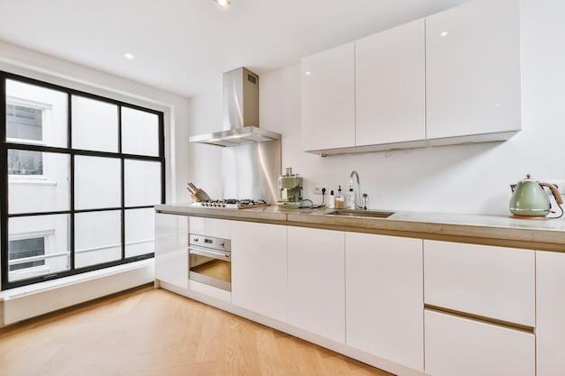 Wnętrze przestronnej kuchni z białymi szafkami i nierdzewnym okapem oraz czarnym blatem