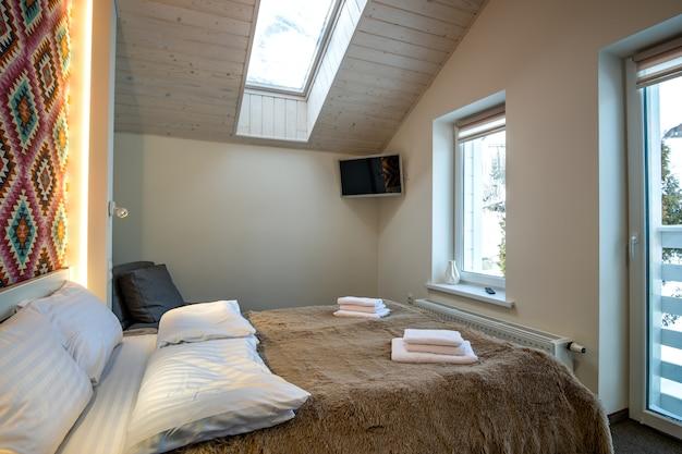 Wnętrze przestronnej sypialni hotelowej na poddaszu ze świeżą pościelą na dużym podwójnym łóżku. przytulny współczesny pokój mansardowy w nowoczesnym domu.