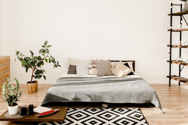 Wnętrze przestronnej sypialni w stylu skandynawskim z szarym łóżkiem i doniczką figową