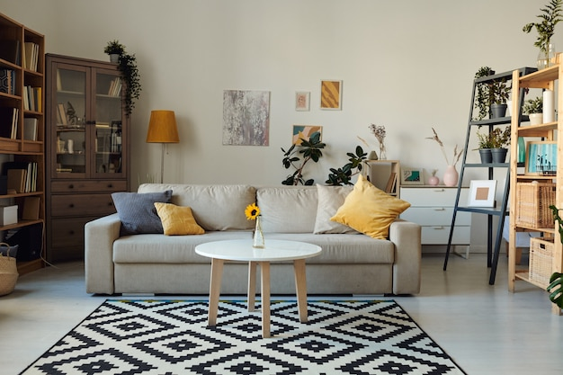 Wnętrze przytulnego salonu ze zdjęciami na ścianie, regały, kanapa z poduszkami i stolik kawowy z wazonem