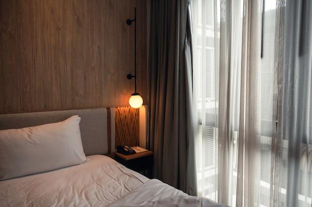 Wnętrze przytulny styl drewnianej sypialni z zasłoną i świecącą lampą