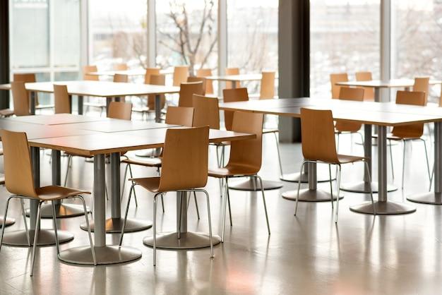 Wnętrze pustej stołówki ze stołami i krzesłami