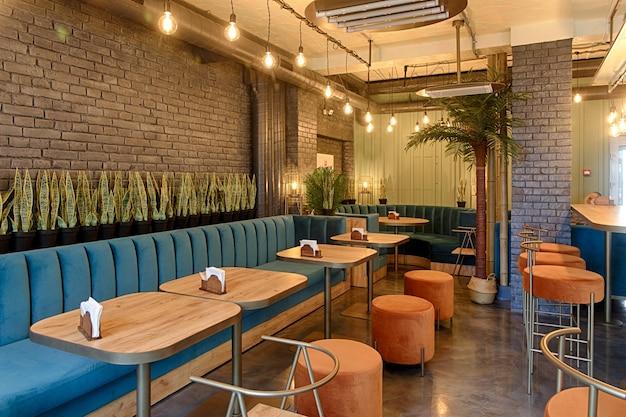 Wnętrze restauracji, nowoczesny design w kilku kolorach, pomarańczowym i niebieskim.