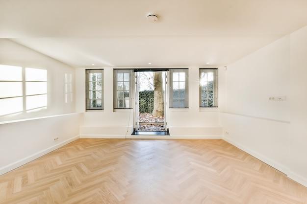 Wnętrze sali lekkiej z parkietem i białymi ścianami z otwartymi drzwiami na podwórko w nasłonecznionym miejscu